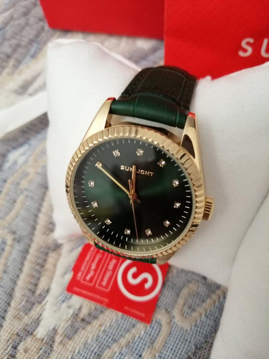 Часы с зеленым ремешком.