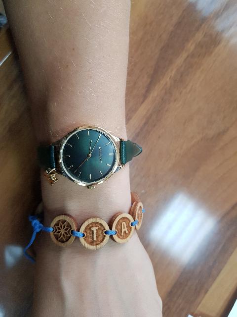 Женские часы с зеленым браслетом.